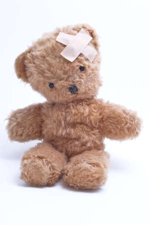 tatty: An old, worn out teddy bear from 1963, light reddish brown with sticking plasters in an x shape on his head. Black eyes and stitched nose. White background.