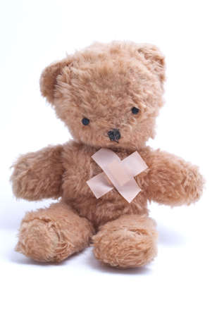 An old, 1960s teddy bear with plasters in an x shape over his heart to represent either injury or lost love.   photo