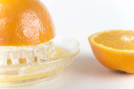 juice squeezer: Half an orange being squeezed on an old style, manual glass juice squeezer, with the remaining half to its right, turned upwards. White background.