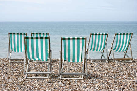 turquise: Rear view of six turquise and white striped deckchairs facing the sea on a pebble beach