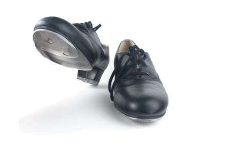 A pair of used black tap shoes with laces, one on the ground and one raised up, ready to step.  White background, shadows visible. Stock Photo