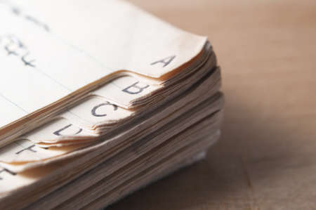 indexed: Close up of an old, index tabbed address book with yellowing and furled pages, placed on a wooden table with light coming from left of frame and some shadow to the right. Stock Photo