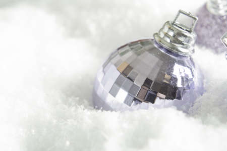 A lilac (light purple) Christmas bauble partly submerged in fake snow.  Snowy surface provides copy space to left and beneath the ornament. photo