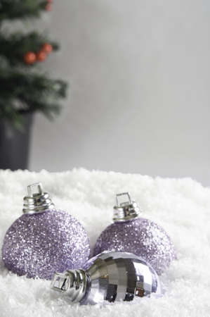 Three Christmas baubles, partly submerged in white snow.  Grey background provides copy space above and right with Christmas tree in soft focus. photo