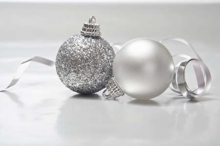 A silver Christmas scene of two baubles (one sparkly, one pearl) on a metallic, softly reflective surface, with a shiny foil ribbon swirling behind.  Copy space in lower part of frame. Stock Photo