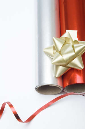 Overhead close up shot of two rolls of Christmas wrapping paper and a gold decorative rosette.  A swirl of shiny red ribbon is placed at the bottom of the frame.  Copy space to left. photo
