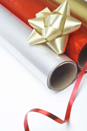 Close up, angled shot of gift wrapping paper rolls, rosette and ribbon on a white surface. Stock Photo