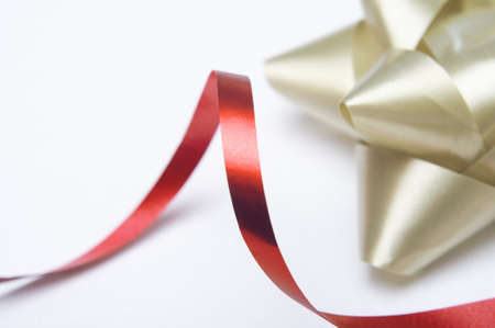 Close of of a swirling red ribbon with a gold decorative rosette in the background.  Shallow depth of field.  White background provides copy space. photo