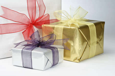 Close up of three gifts, wrapped in white and metallic foil papers, tied with ribbons and knotted with bows. Stock Photo