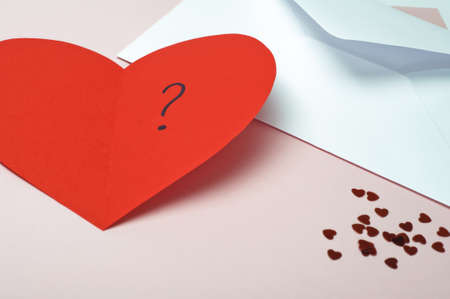 scattered in heart shaped: A red heart-shaped Valentines card, opened to reveal a question mark.  Small metallic hearts scattered at bottom right, with white open envelope at top right.  Pink background with copy space.