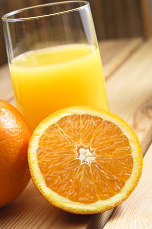 Close up of a glass of orange juice with cut and whole oranges on wooden table. Stock Photo