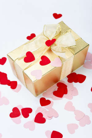 A gold gift box, bow tied with organza ribbon, sprinkled with pink and red paper heart-shaped confetti. photo