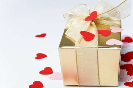 Close up of a gold gift box, tied and bowed with organza ribbon and scattered with pink and red paper heart confetti.  Background is off-white. photo
