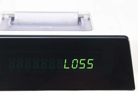 Close up of a calculator screen showing the word loss in bright green simulated LED.  Paper roll is visible in soft focus background. photo