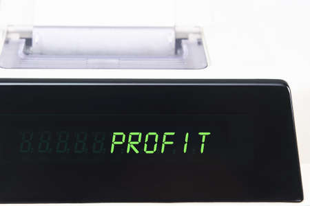 Close up of a calculator screen showing the word profit in bright green simulated LED.  Paper roll is visible in soft focus background. photo