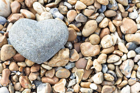 A grey heart shaped stone in upper left of frame, resting on a variety of smaller stones.  Landscape (horizontal) orientation.