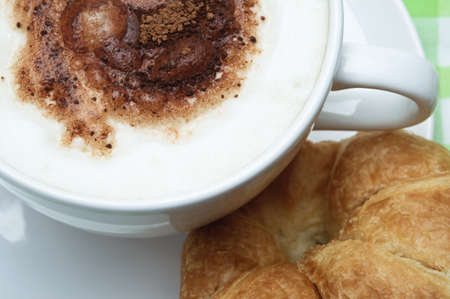 Overhead close up of a cup of coffee with frothed milk and cocoa sprinkles, on a saucer with a croissant.  Gingham tablecloth in background. photo