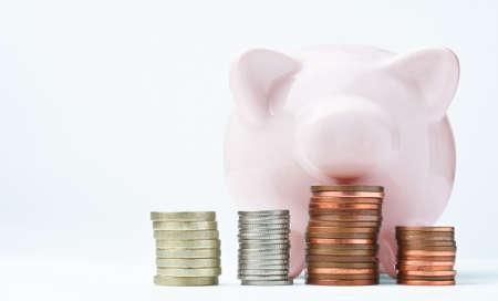 ピンクの貯金、正面を向いて、上にいくつか探してコイン スタック。使用される硬貨がイギリス、レタリングは一般的な使用を有効にする削除され 写真素材