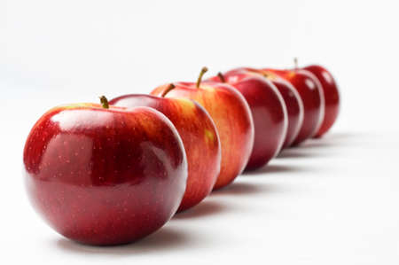 Close up of a row of seven shiny red apples leading away from the viewer at an oblique apple.