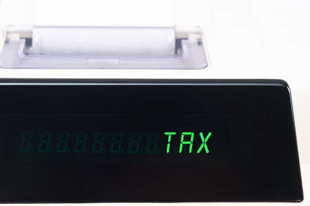 Close up of an LED calculator screen, displaying the word TAX in capital letters. photo