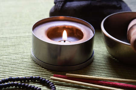 Close up of a collection of Buddhist's objects (candle, josticks, prayer beads and singing bowl), with part of a Buddha statue in the background. Placed on an olive green ribbed mat.