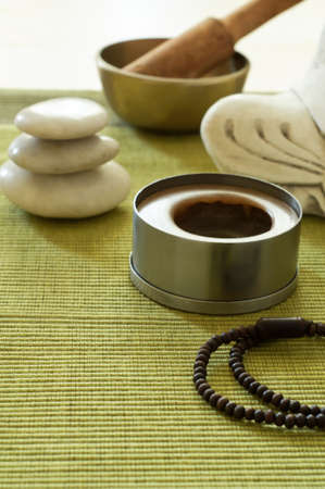 A setting for Buddhist meditation with stacked Zen stones, singing bowl, unlit candle Buddha statue (cropped) and prayer beads on a ribbed green mat.   Light wood table surface just visible at top of frame. photo