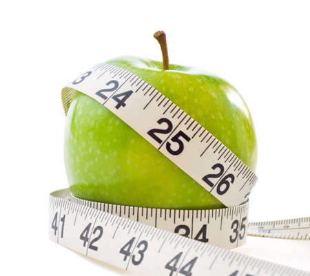 measuring tape: A green shiny Apple, wrapped with a white measuring tape to signify dieting and weight loss.  Isolated on white background with light shadows retained.
