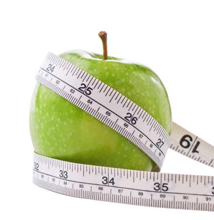 retained: Una brillante manzana verde, envuelta con una m�trica blanco y imperial medir la cinta para significar la p�rdida de peso y dieta.  Aislados en fondo blanco con sombras leves retenidas.