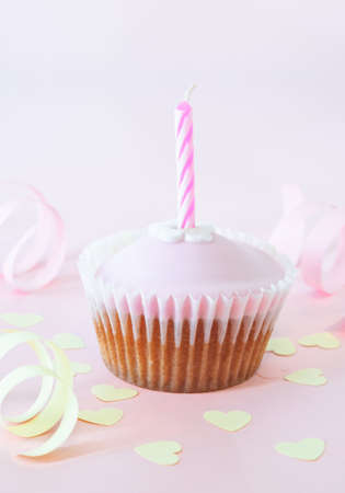 An iced cup cake with birthday candle on pink background with yellow heart confetti and curled paper streamers. photo