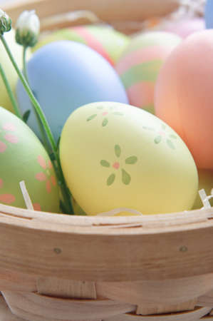 Close up of decorated Easter eggs (hand painted by the photographer) in a woven wooden basket with paper straw and budding flowers.  Shallow depth of field. photo