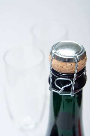 bottleneck: Close up of a sealed champagne cork and bottleneck, with two fluted glasses in soft focus behind.