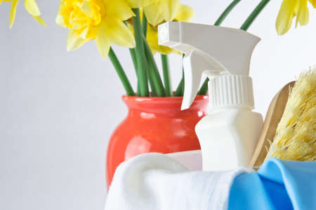 Horizontal shot of cleaning items in foreground with vase of daffodils in background to indicate Spring time. Stock Photo