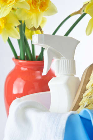 Vertical shot with cleaning products in the foreground and a vase of daffodils in the background to indicate Spring. Imagens