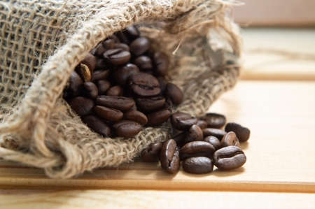 Close up of a hessian sack containing whole coffee beans, spilling on to wooden table.