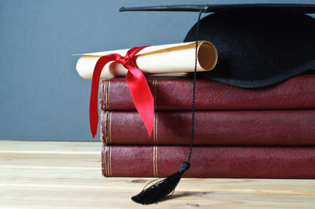 Graduation mortarboard and scroll tied with red ribbon on top of a stack of old, worn books on a light wood table.  Grey background.   photo