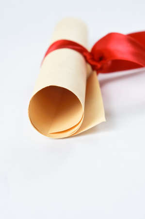 A rolled scroll of parchment coloured paper, tied with red ribbon to signify a diploma or award. Stock Photo