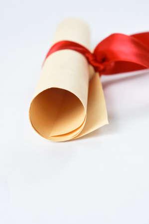 Un défilement laminé de parchemin de couleur papier, à égalité avec ruban rouge pour signifier un diplôme ou un prix.