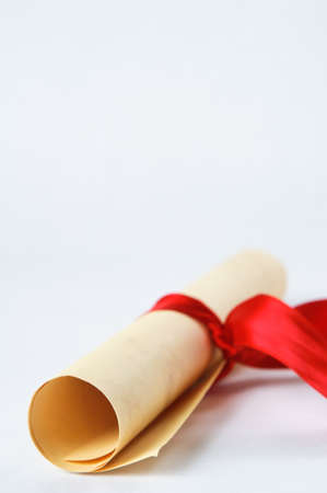 parchment scroll: A rolled up parchment scroll, tied with a red ribbon to suggest graduation diploma or award. Stock Photo