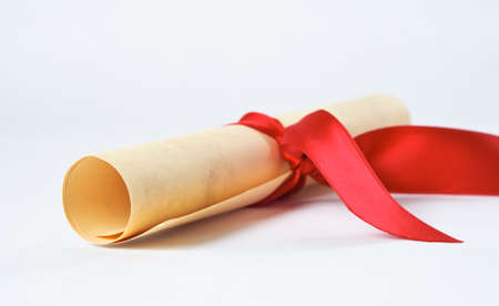 Close up of a rolled up diploma scroll, tied with a red ribbon. photo