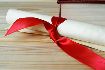 A scroll tied with red ribbon on a wooden surface in front of a book, to illustrate diploma or degree.