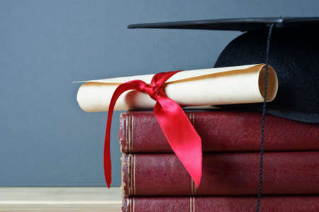 Close up of a mortarboard and graduation scroll on top of a pile of old, worn books, placed on a light wood table with a grey background. Stock Photo