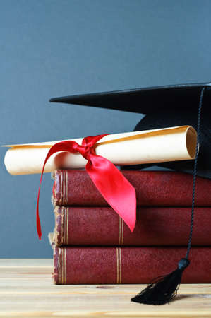 A stack of old, worn books with a mortarboard and ribbon tied scroll on top, placed on a wooden table with a grey background. Stock Photo