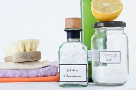scrubbing: A range of non-toxic cleaning products in glass jars and bottles with a stack of cleaning cloths and scrubbing brush.  Copy space upper left.