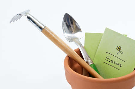 Close up of a terracotta plant pot containing seed packet and potting tools. Stock Photo
