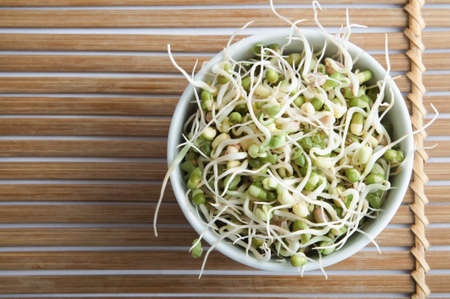 Overhead shot of a bowl of mung beansprouts, standing on a slatted bamboo mat.