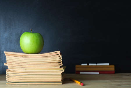 schoolgebouw: A school teachers desk with stack of exercise books and apple in left frame. A blank blackboard in soft focus background provides copy space. Stockfoto