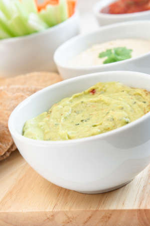 Guacamole, hummus and salsa dips in white bowls on a wooden board with wholemeal pitta bread and crudites cropped at left frame.