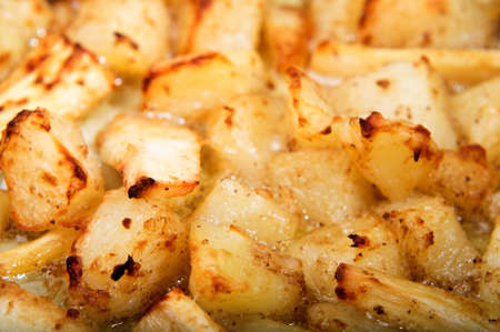 Crispy roasting potatoes and parsnips in bubbling oil, filling the frame.  Horizontal (landscape) orientation. Stock Photo - 9948025