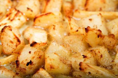 Crispy torrefazione di patate e pastinaca in olio gorgogliante, riempiendo il telaio.  Orientamento orizzontale (paesaggio).
