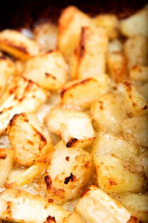 Pastinaca in olio caldo, spumeggiante e patate arrosto croccante.  Orientamento verticale (ritratto).